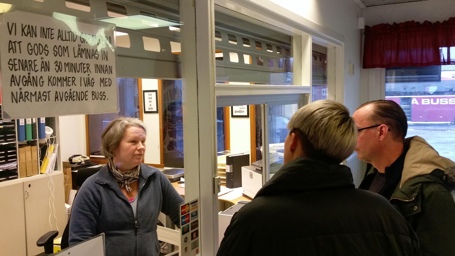 Två personer står och pratar med en kvinna som jobbar på Sorsele busstation.