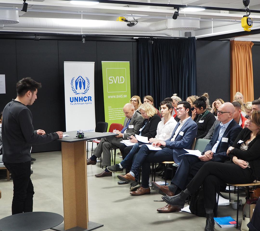 En ung kille står vid ett podium och pratar inför en publik.