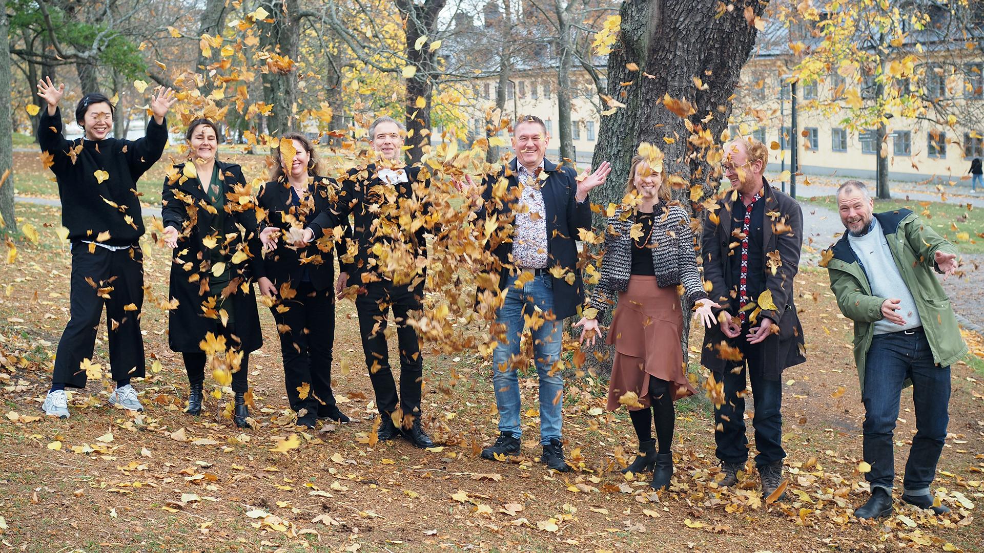 Personal från SVID som kastar löv i luften.