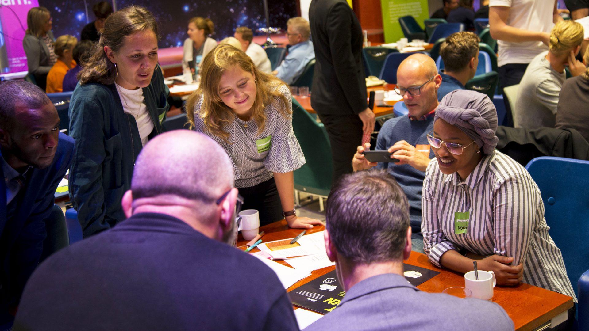 Personer som sitter runt ett bord och jobbar och diskuterar.