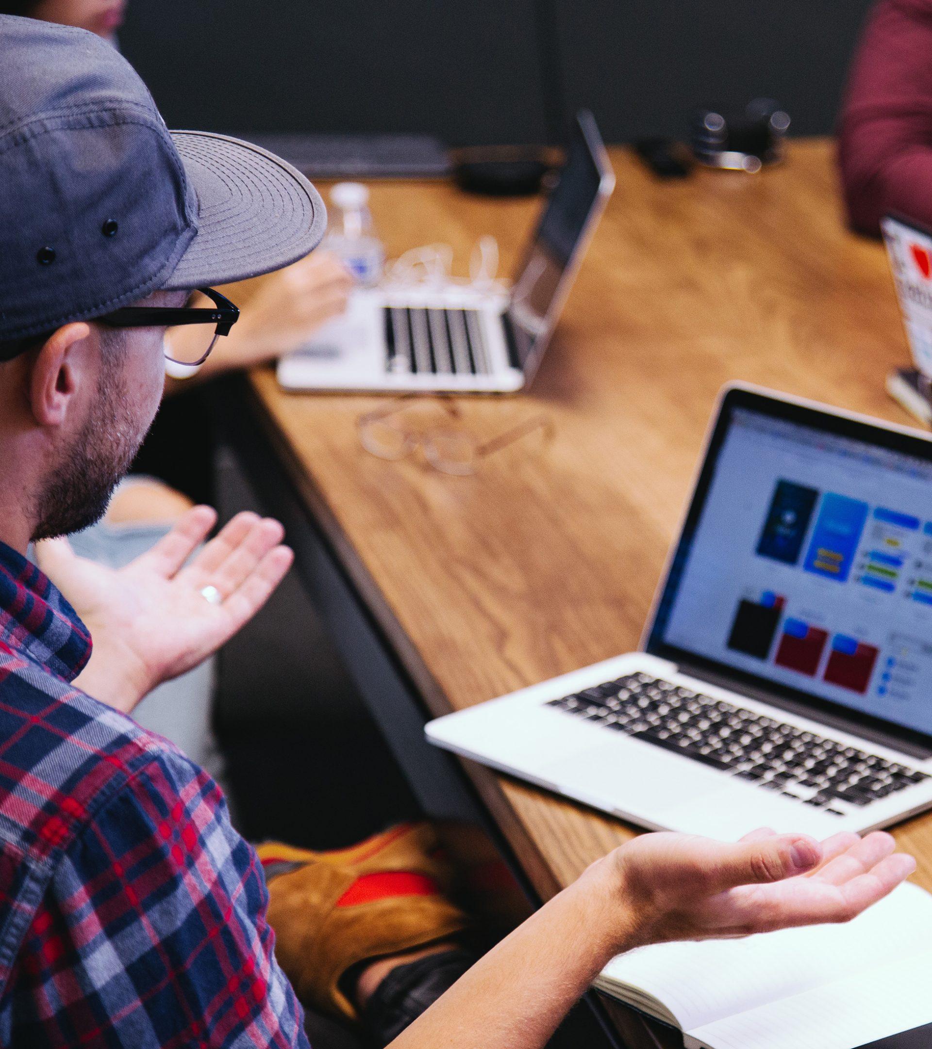 Person som sitter och pratar vid ett bord med andra personer runt omkring. Datorer på bordet.