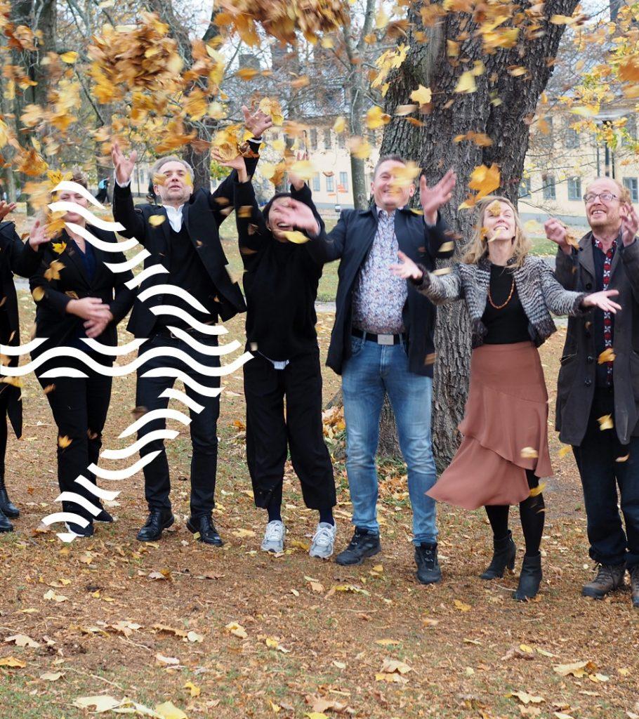 Medarbetare från SVID som kastar löv i luften. Illustrerad pil på bilden.