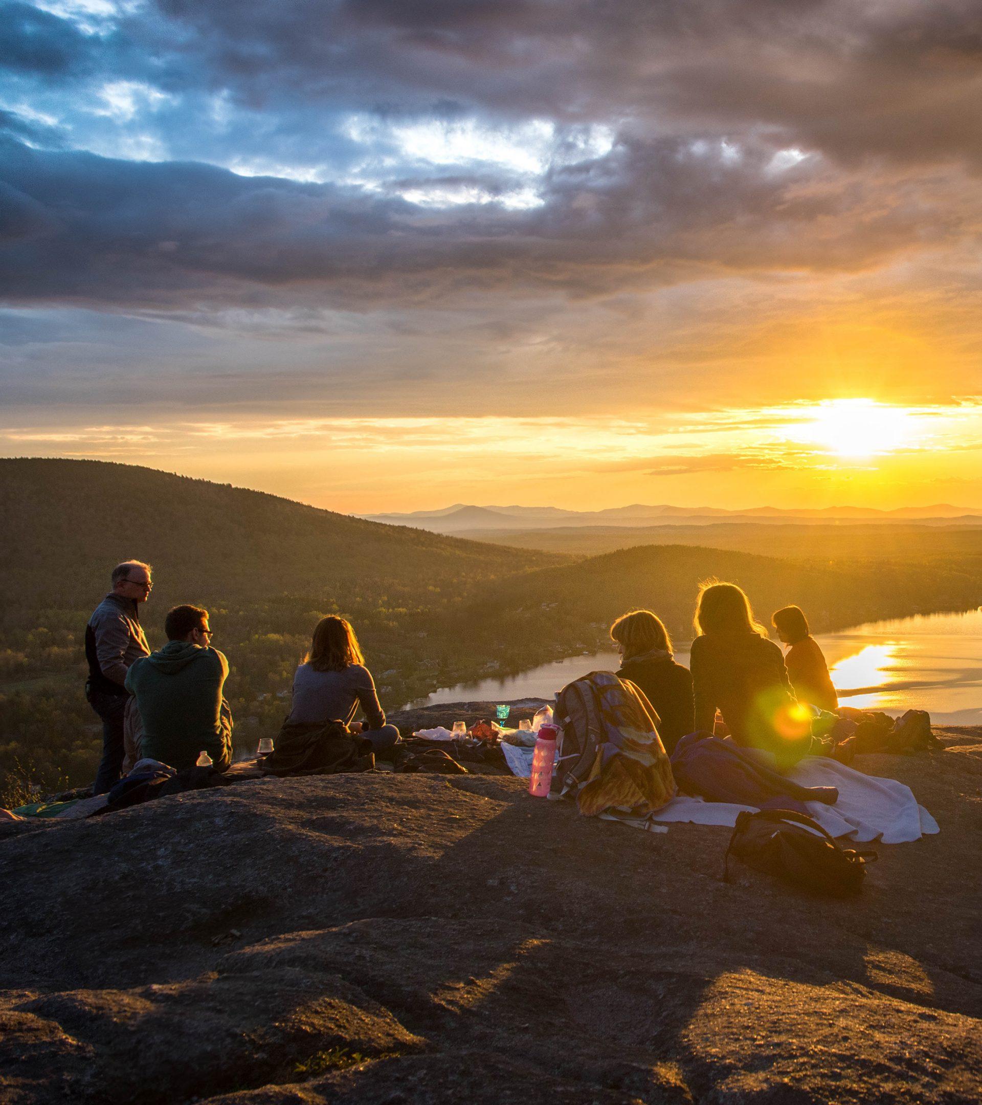 Personer som sitter på ett berg och har picknick. Solnedgång och utsikt över en sjö.