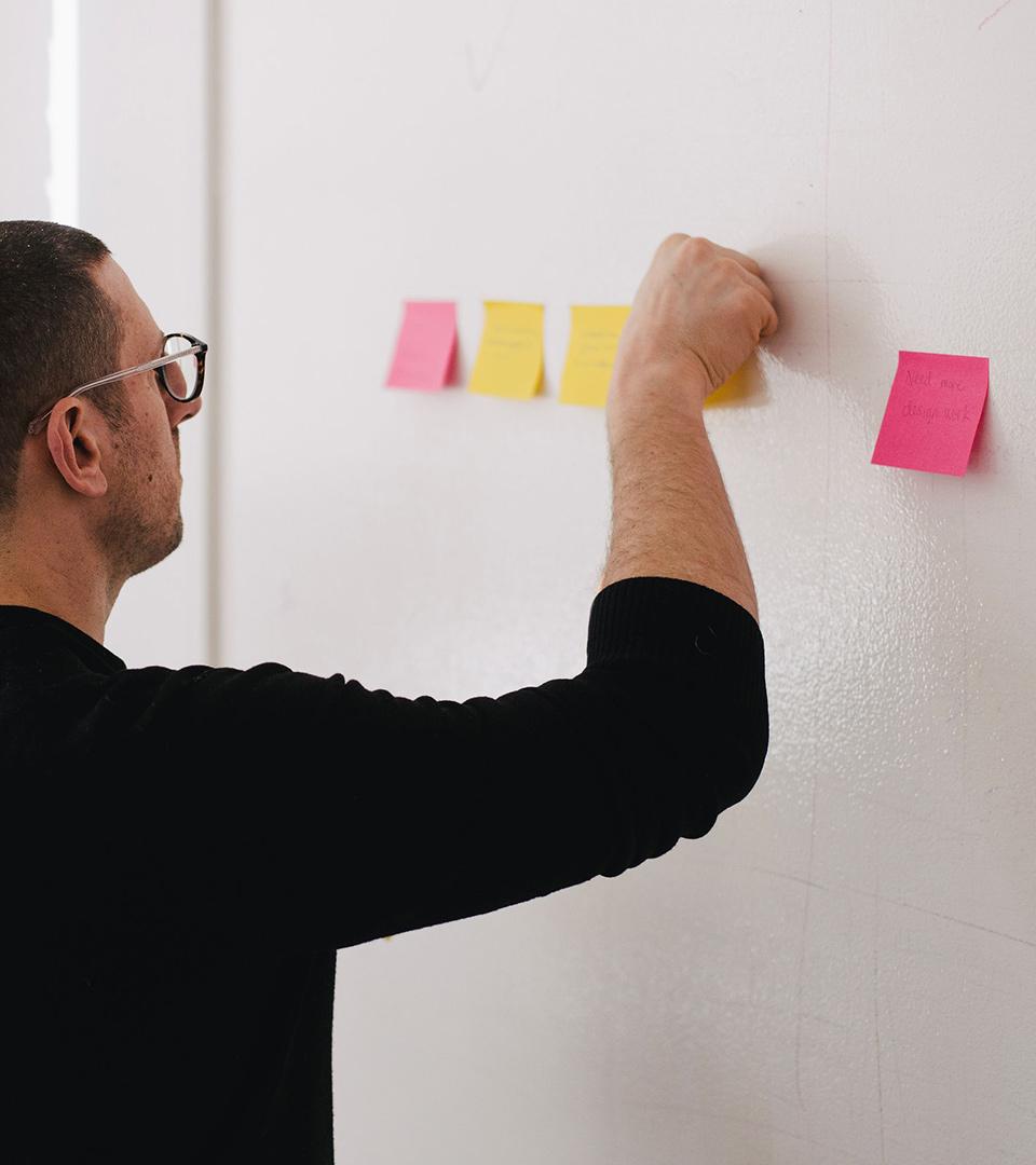 Person som sätter upp post-its på en vägg