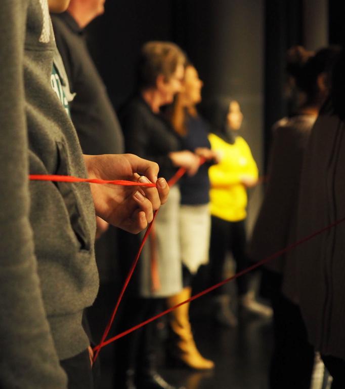 Personer som håller i en röd tråd.
