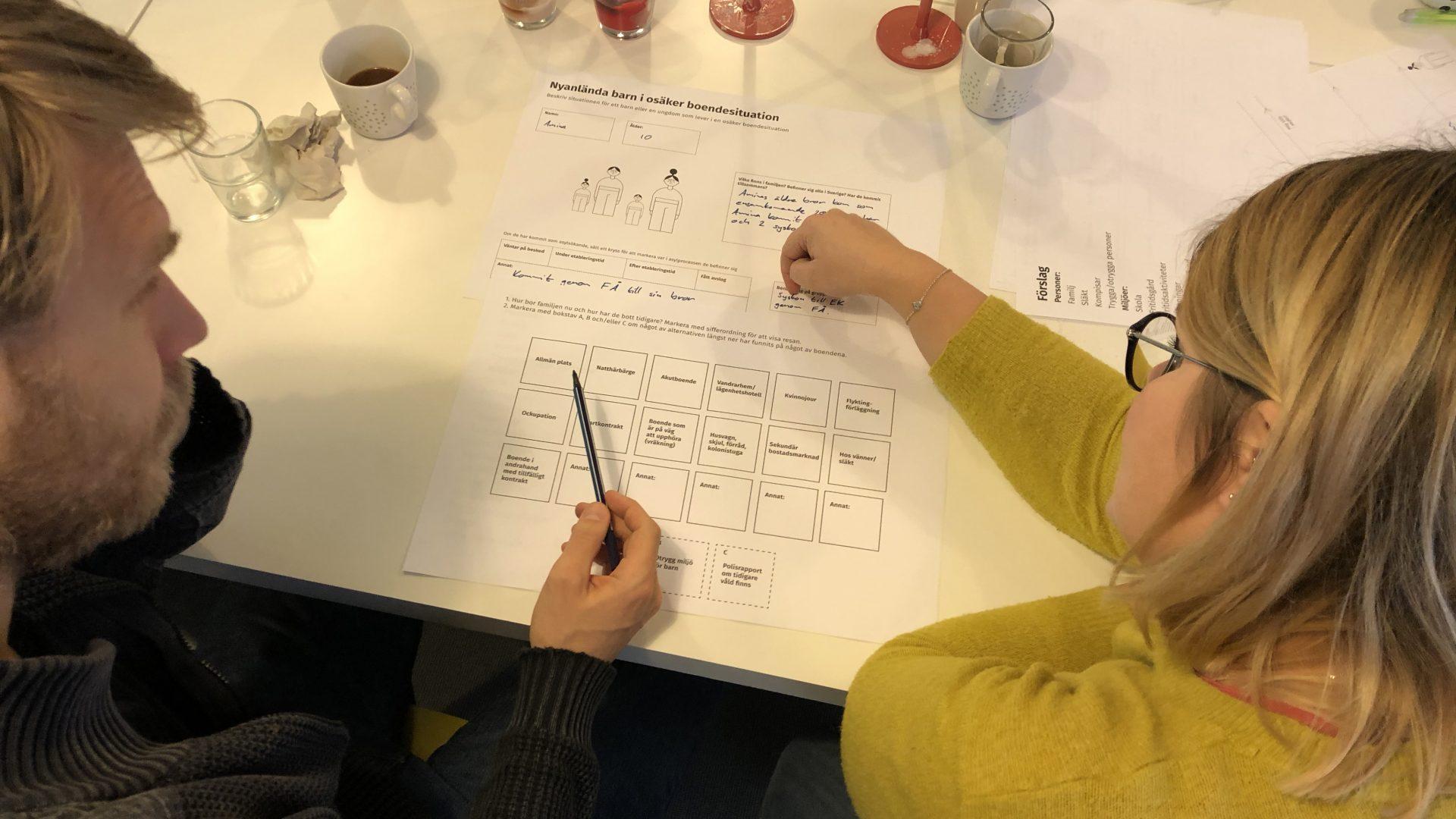 Personer som sitter och diskuterar och fyller i uppgifter på ett papper.