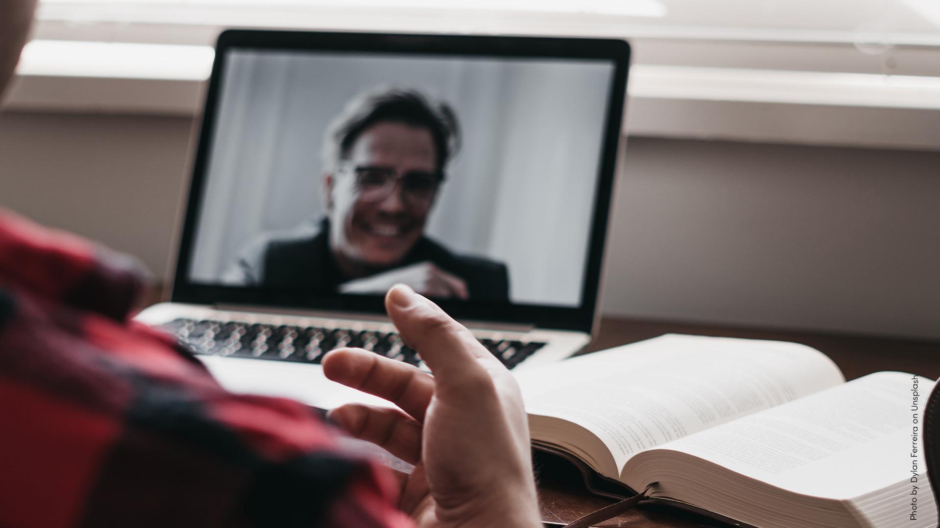 Person som sitter vid sin laptop och har ett digitalt möte.