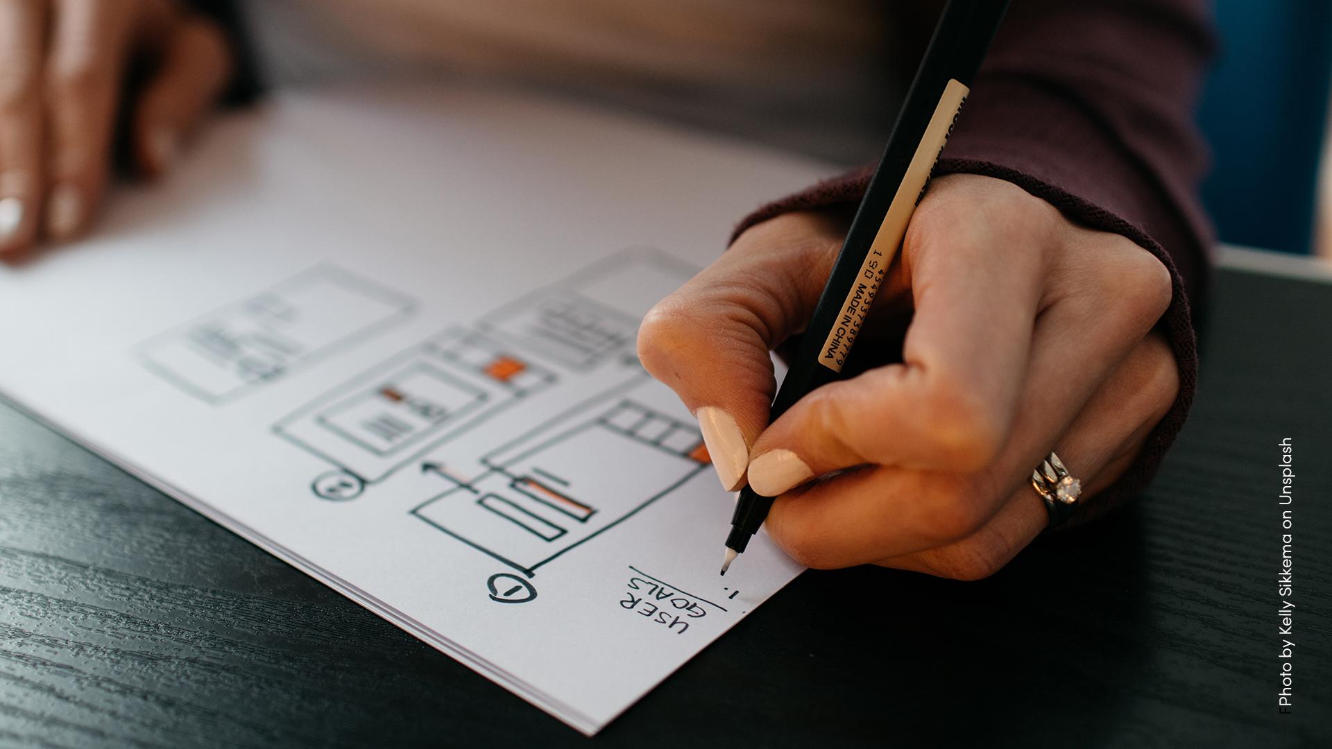 Person som ritar på ett papper. Man ser endast händerna och papperet på ett bord.