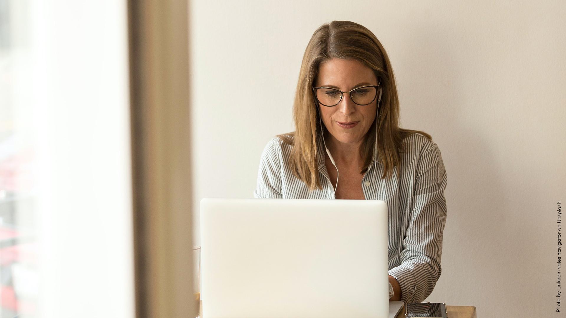 Kvinna som sitter vid en laptop och skriver.