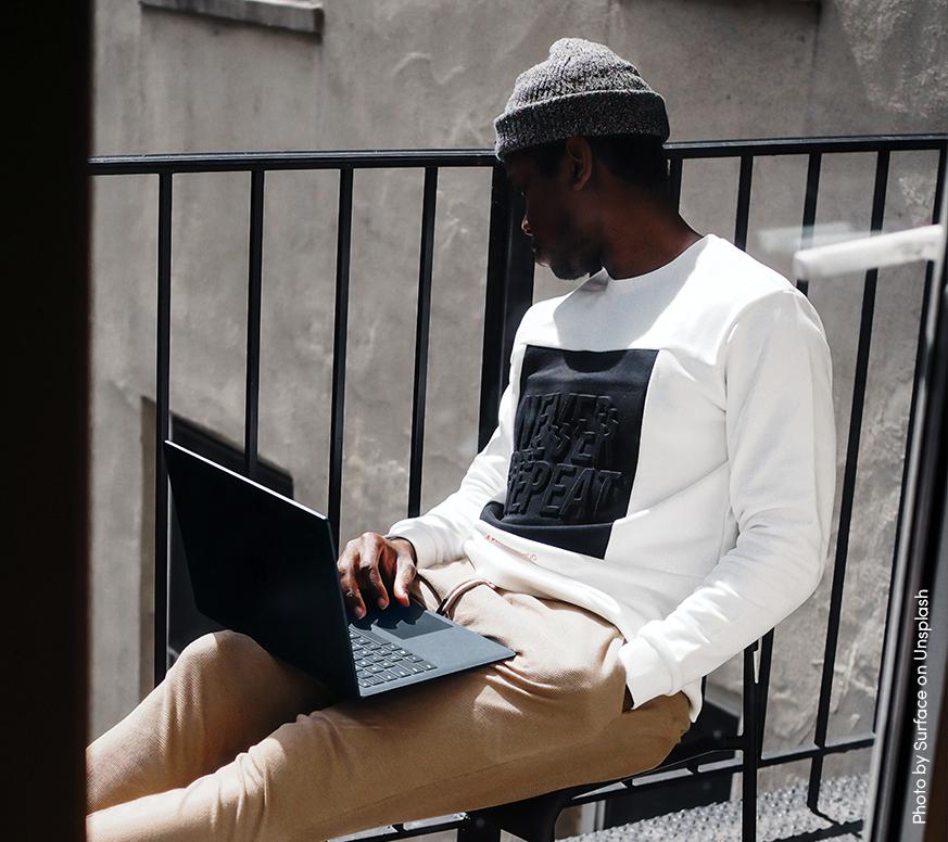 En kille som sitter på en balkong med en laptop i knät. Tittar ut över balkongräcket.