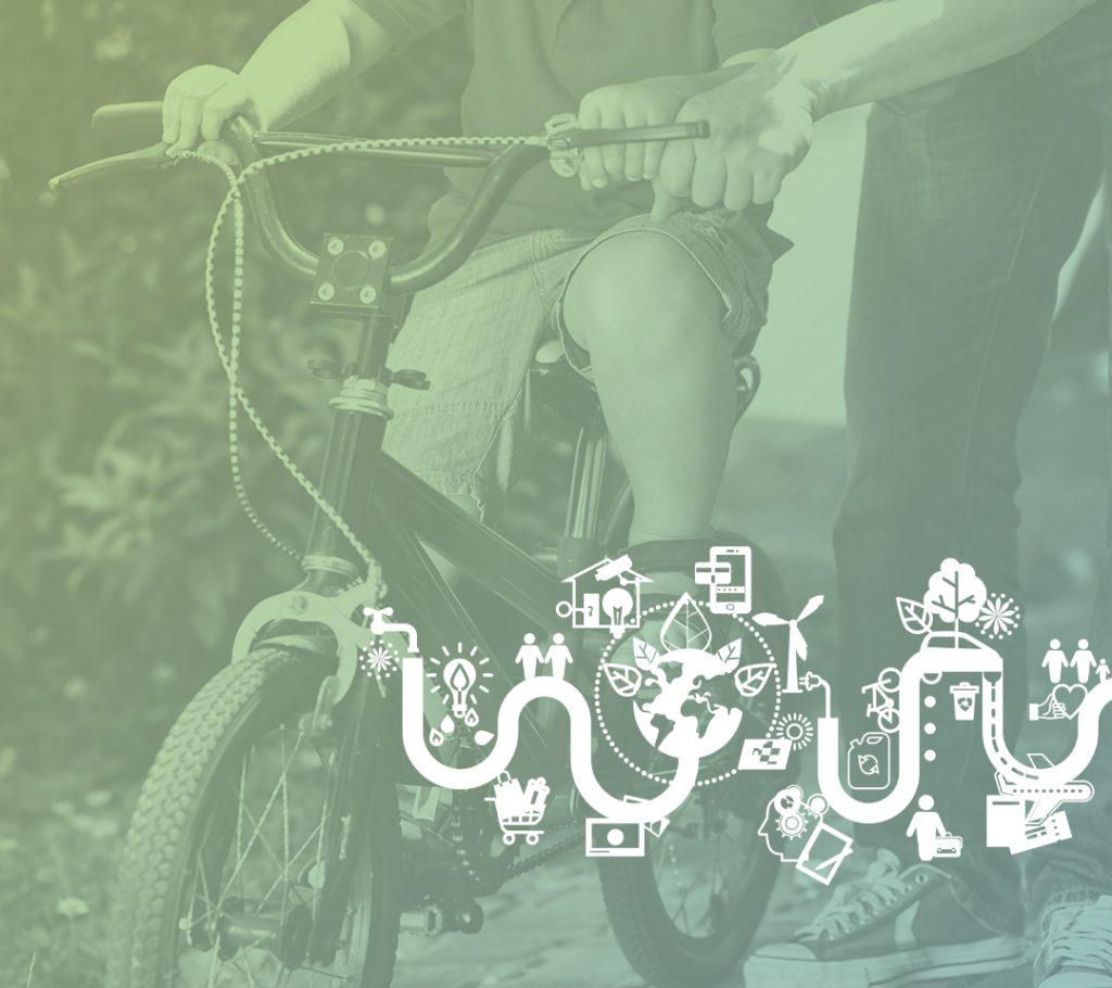 Pojke som cyklar och förälder som hjälper till och håller i styret.