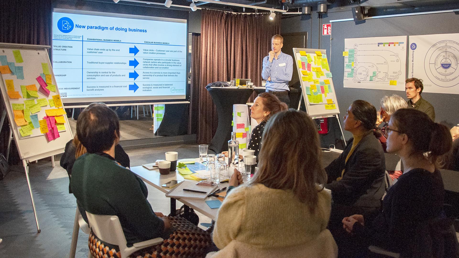 En person som framme vid en skärm med en presentation, och redovisar inför en grupp människor som sitter vid bord framför.