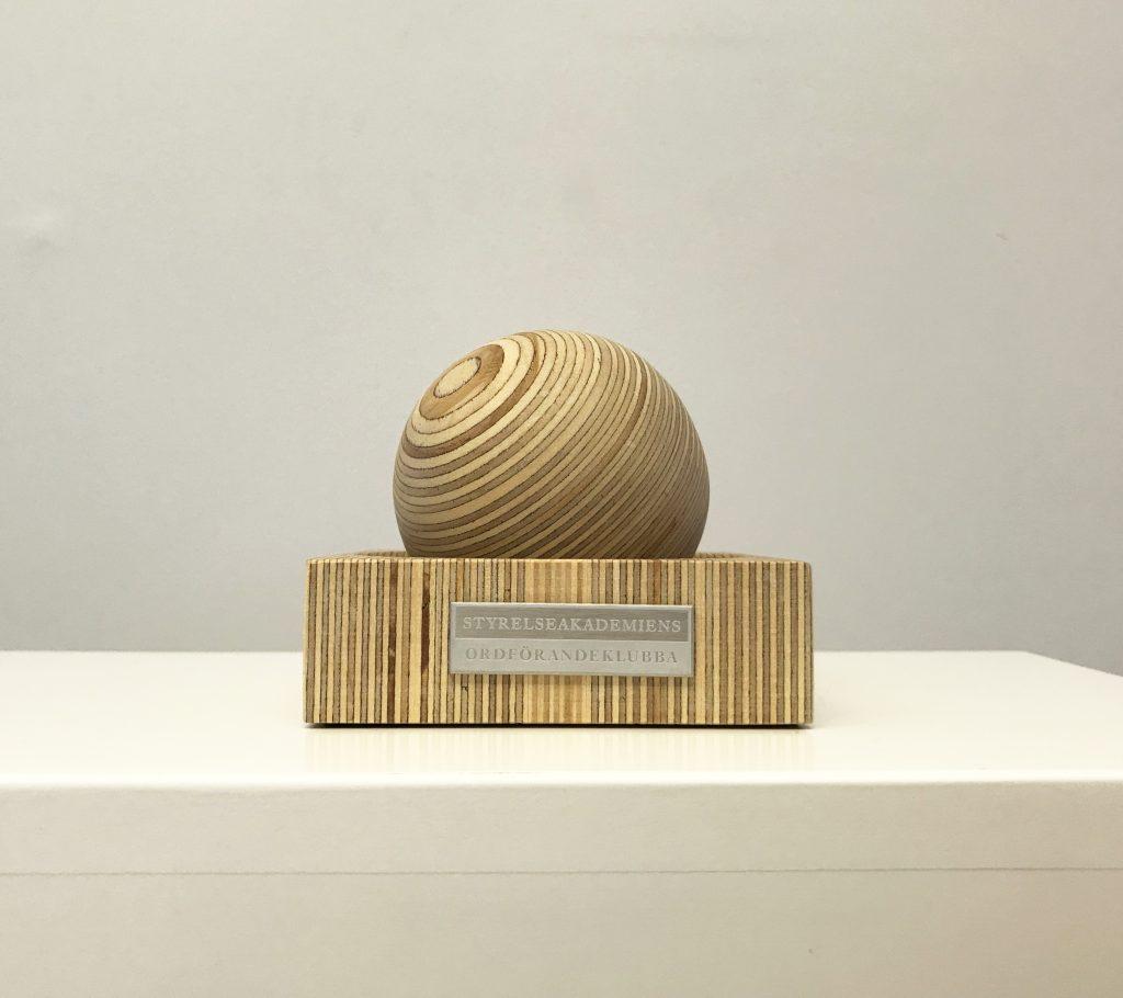 En mötesklubba i form av en rund kula i trä som ligger i en träskål.