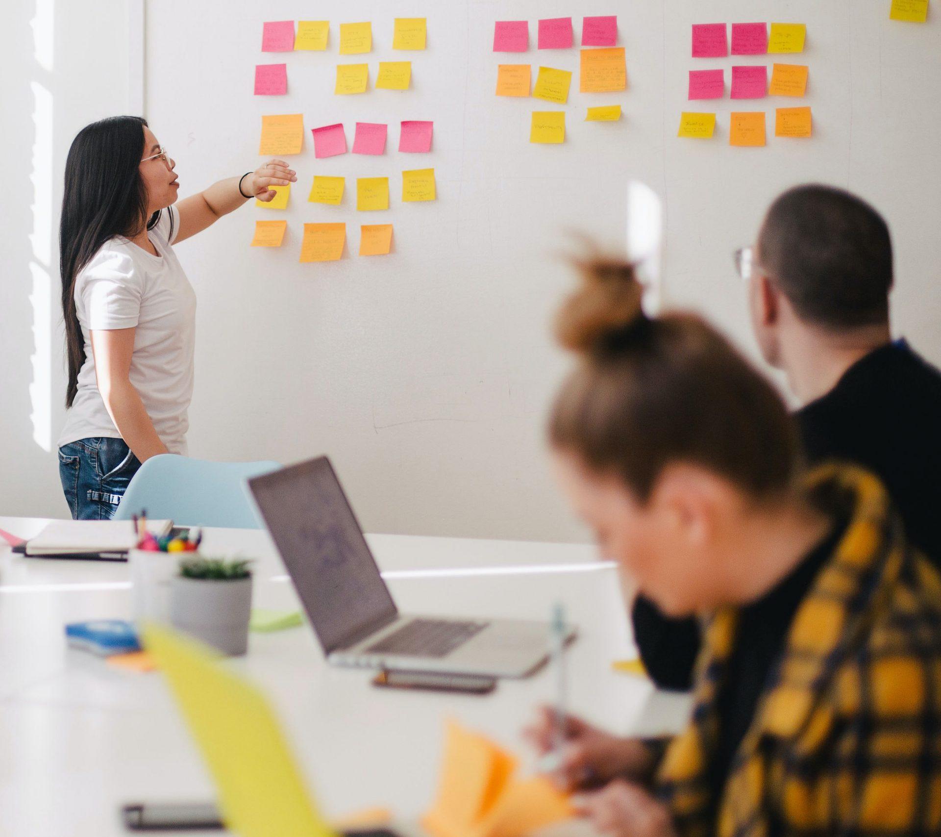 Kvinna som står längst fram vid en whiteboard och pekar på post-its. En kille och en tjej sitter vid ett bord i förgrunden.