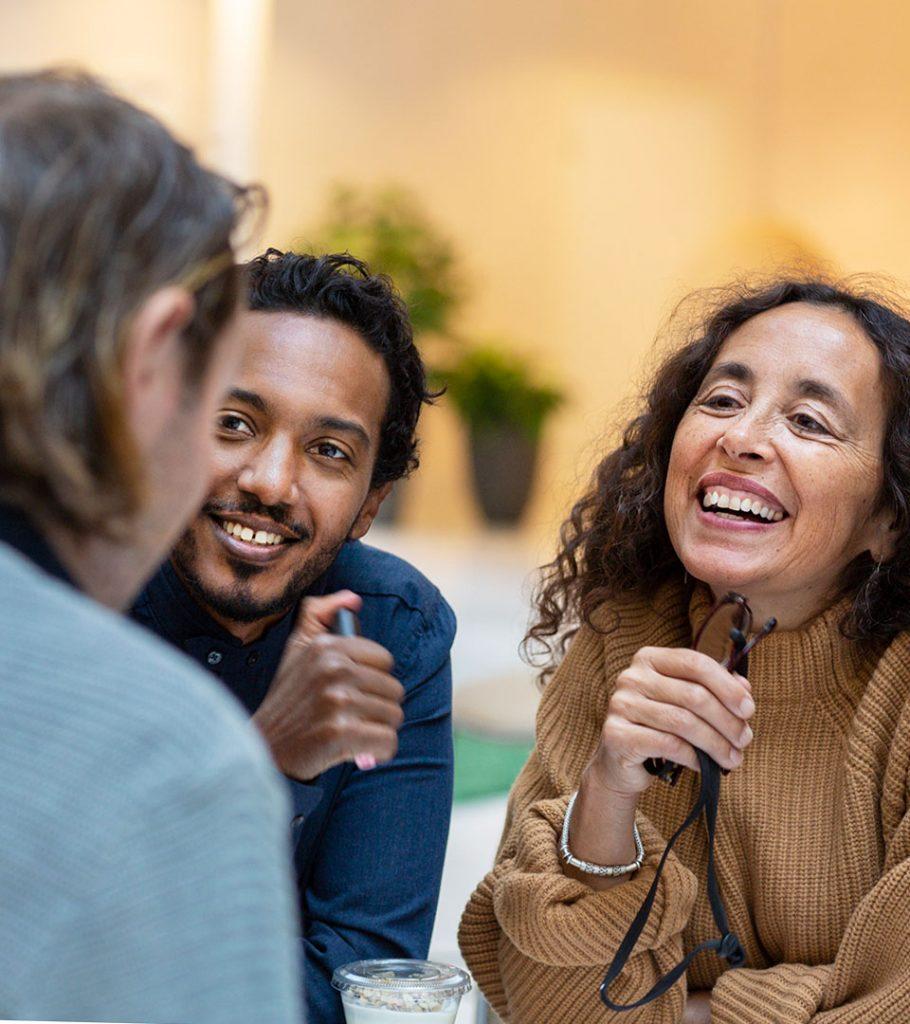 Grupp som sitter vid ett bord. Glad man och glad kvinna.
