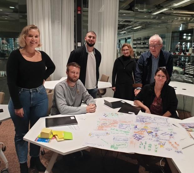 Bild inomhus på sex personer som står och sitter vid ett bord. På bordet ligger stora papper som det är ritat och skrivet på.