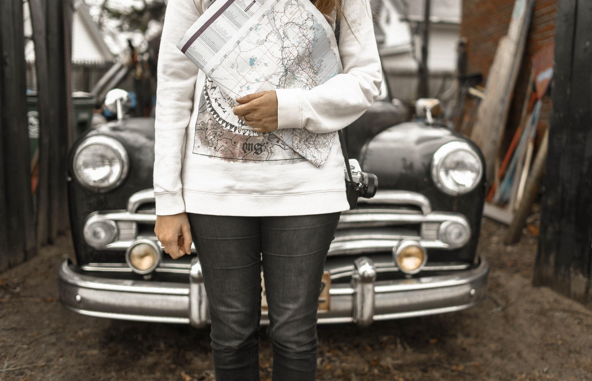 Person som håller i en karta, och står framför en bil. bild