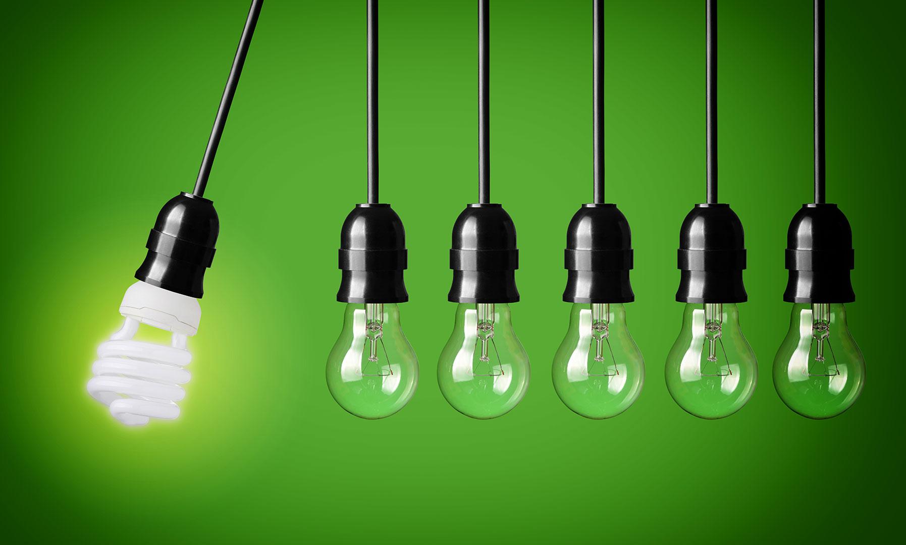 Bild inomhus på glödlampor som hänger ner i svarta sladdar. En av lamporna lyser och svänger ut åt sidan. Väggen bakom lamporna är grön.