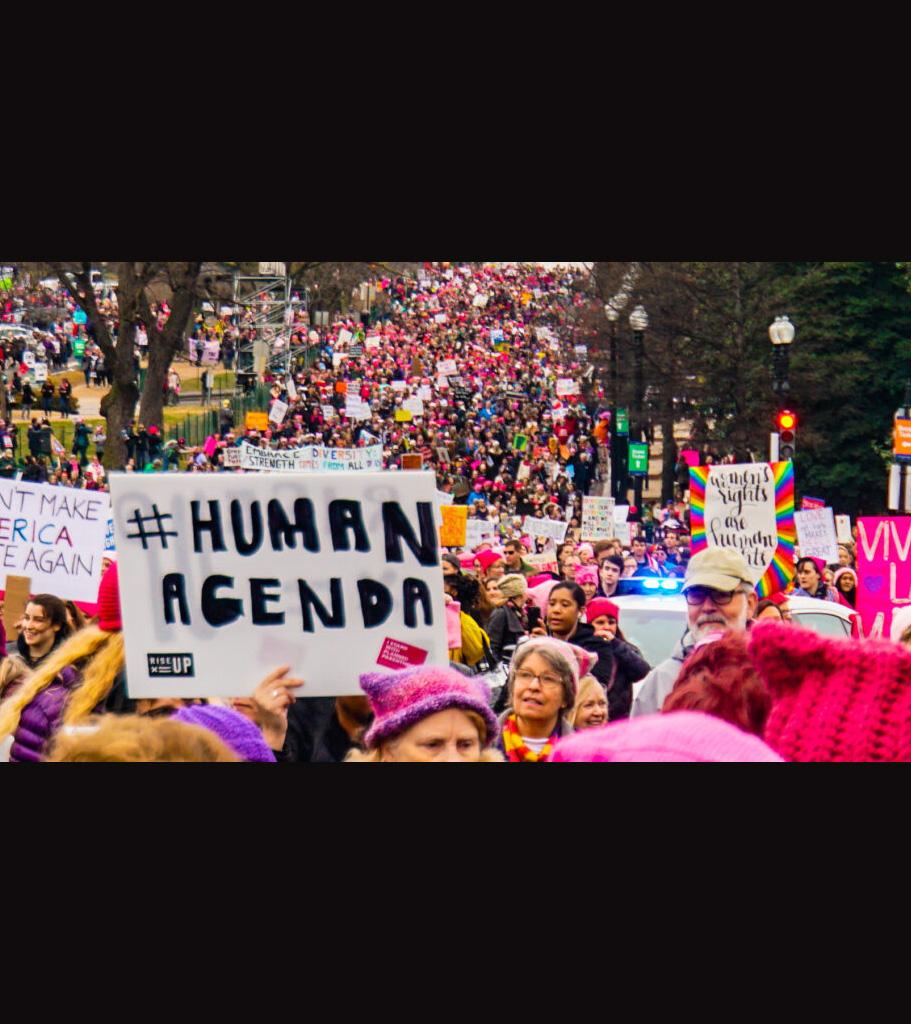 Massor av människor som paraderar i en demonstration. Skylt med texten #human agenda