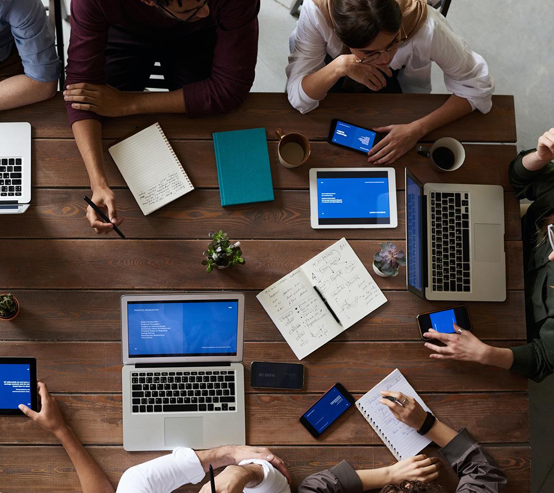 Personer som sitter runt ett bord och diskuterar. På bordet ligger datorer och skrivblock.