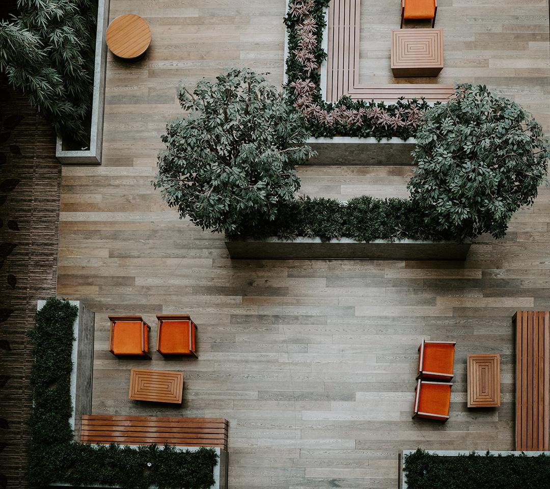 Foto uppifrån en ljushall med möbler och växter.